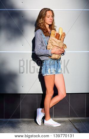 Stylish Blonde Woman Hipster Is Holding In Their Hands A Paper Bag With Baguettes