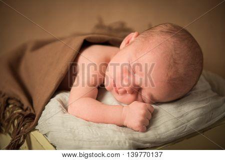 Newborn baby sleeping in a bucket. Close-up