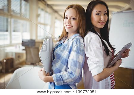 Portrait of female colleagues standing back to back in creative office