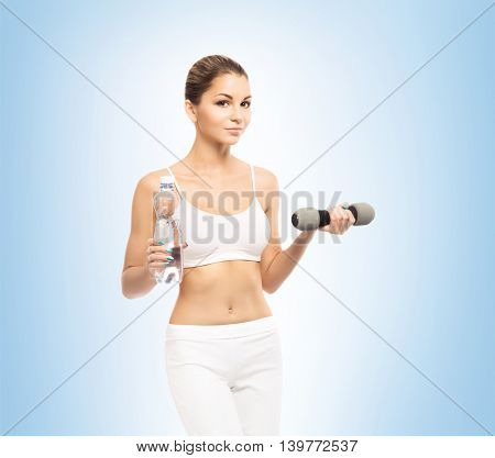 Sporty, athletic and attractive woman with a dumbbells over blue background. Sport, dieting and healthy lifestyle concept.