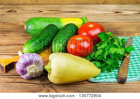 Backyard vegetables tomatoes cucumber garlic pepper and parsley on board wooden background