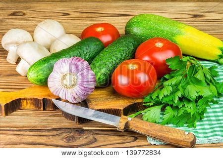 Backyard vegetables tomatoes cucumber garlic mushrooms and parsley on board wooden background