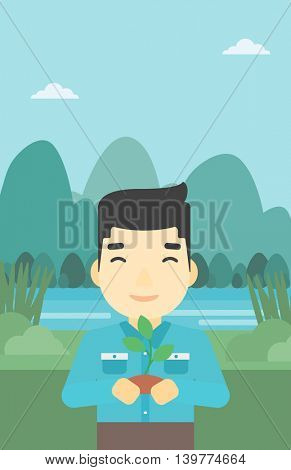 An asian young man holding in hands a small plant in soil on the background of landscape with mountains and river. Vector flat design illustration. Vertical layout.