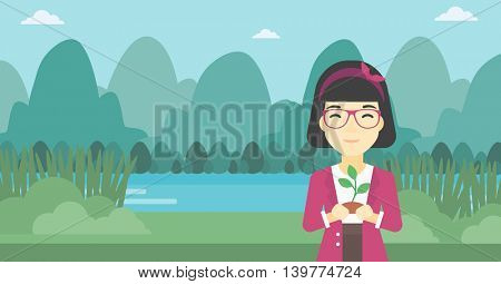 An asian young woman holding in hands a small plant in soil on the background of landscape with mountains and river. Vector flat design illustration. Horizontal layout.
