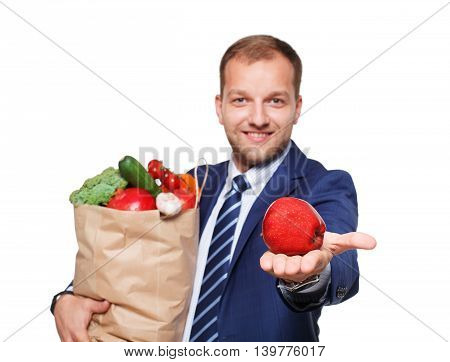 Smiling young businessman hold shopping bag full of groceries isolated at white background. Healthy food shopping. Paper package with vegetables and fruits, happy man buyer show red apple