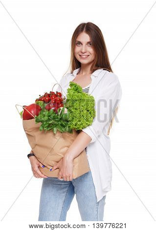 Smiling young woman holding shopping bag full of groceries isolated at white background. Healthy food shopping. Paper package with vegetables and fruits, happy female buyer came from market