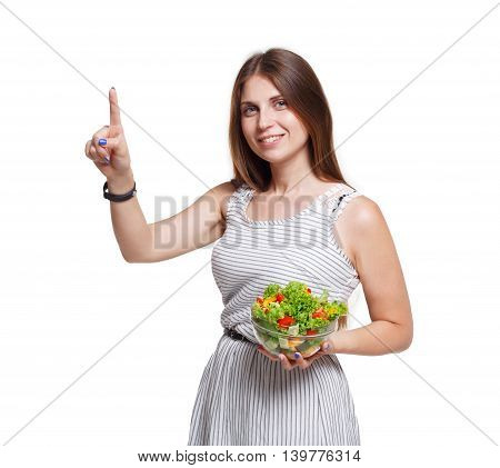 Healthy food and diet concept. Young smiling woman holding fresh vegetable salad meal and touch imaginary screen or push button isolated on white background. Modern dieting and weight loss nutrition