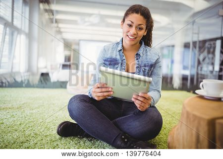 Portait of businesswoman using digital tablet while sitting on carpet in creative office