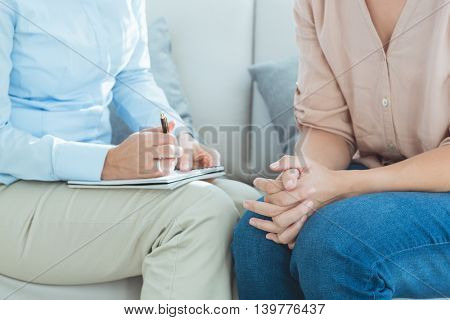Midsection of therapist with patient on sofa at home
