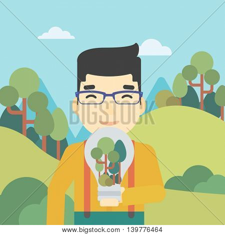 An asian man standing on the background of green forest and holding in hands a big lightbulb with trees inside. Green energy concept. Vector flat design illustration. Square layout.
