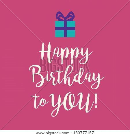 Cute Happy Birthday to You card with a handwritten text and an blue wrapped birthday gift with purple ribbon bow on a pink background.