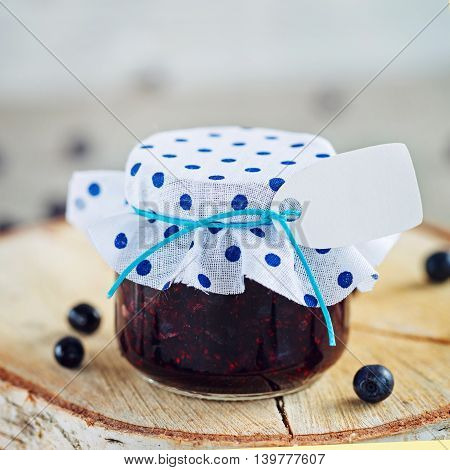 Fresh blueberry homemade jam in jar with tag and berry on  wood background. Healthy organic and vegan food.Toned image. Square