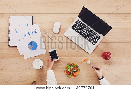 Healthy business lunch of woman at working place. Businesswoman's hands eating in office. Diet food, vegetable salad with apple and juice. Cell phone, laptop and papers. Top view, flat lay