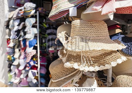 Woman's straw hats for sale at a market.