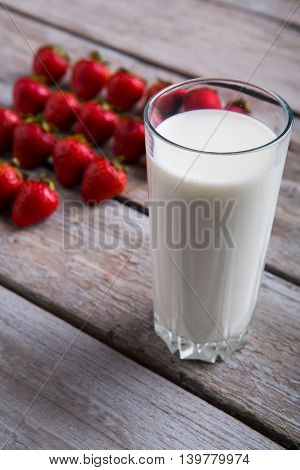 Glass of milk and strawberries. Berries on gray wooden background. Vitamins and calcium. Dessert after breakfast.