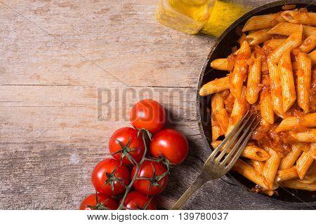 Penne Pasta tagliatellei with tomato sauce on wooden table