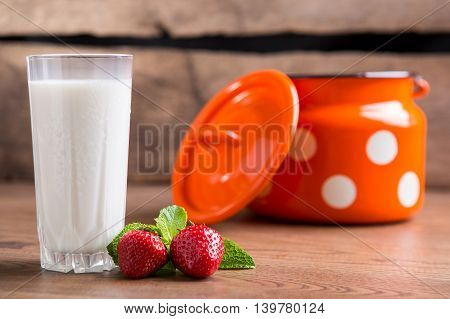 Strawberries and glass of milk. Orange milk can. Make a fruit drink. Nutrition is key to health.