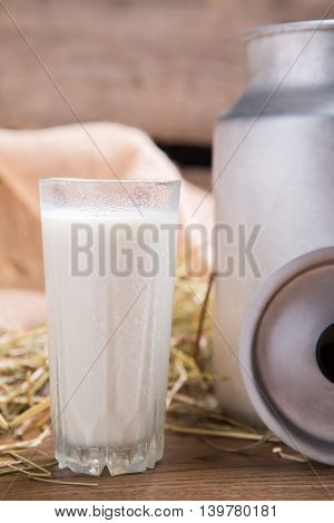 Glass of milk. Milk can and hay. Drink rich in minerals. Health of bones.