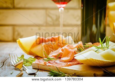 Concept of italian food with red wine, melon and prosciutto on cutting board