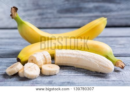 Peeled and sliced banana. Bananas on gray wooden backround. Sweet food high in calories. Fruit of tropics.