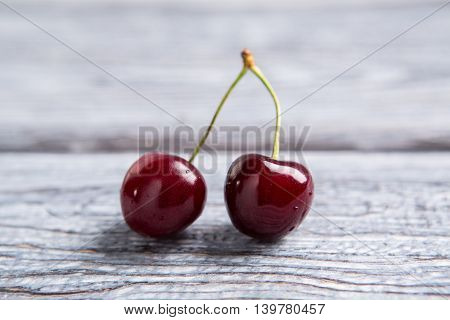 Pair of dark red cherries. Berries on gray wooden background. Key ingredient for vegetarian dessert. Nature created perfection.