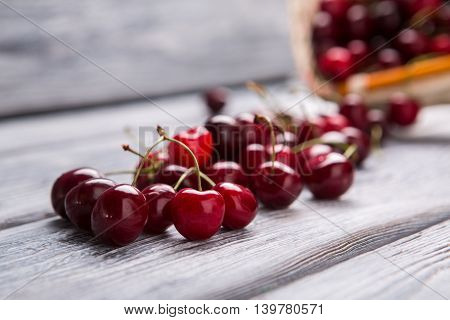 Cherries on wooden surface. Fruit of dark red color. Improve liver health. Vitamins strengthen our organism.