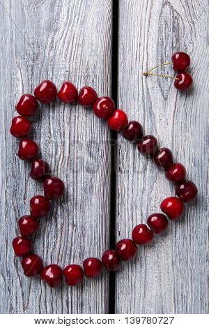 Heart made of red cherries. Fruit on wooden background. Symbol of love. Taste and health.