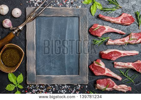 Raw lamb chops with salt, pepper and rosemary over black background. chalk board near. Top view,  copy space.