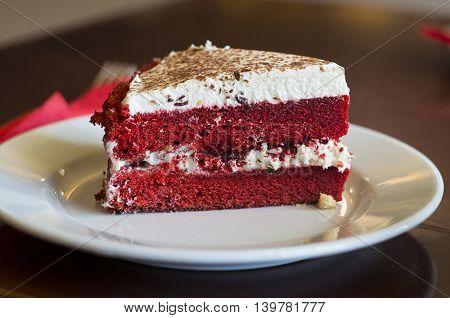 A slice of red velvet cake on a saucer.