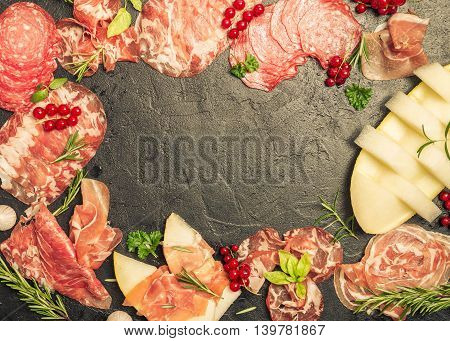 Meat appetizer selection. Italian ham, prosciutto and salami with melon. Ingredients for bruschetta, crostini or sandwich bar, top view, copy space.
