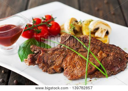 Grilled meat with vegetables and red sauce on wooden background. Served steak with potato, mushrooms and cherry tomato with ketchup, countryside restaurant