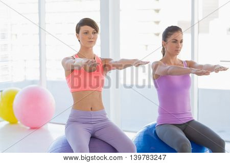 Beautiful women sitting on exercise ball at fitness studio