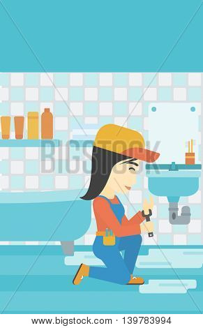 An asian female plumber sitting in a bathroom and repairing sink pipe. Plumber with wrench repairing a broken sink in bathroom. Vertical layout.
