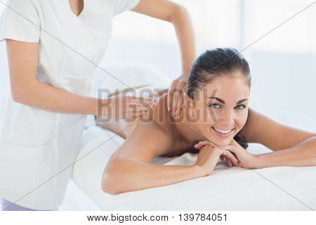 Portrait of smiling woman receiving back massage at spa