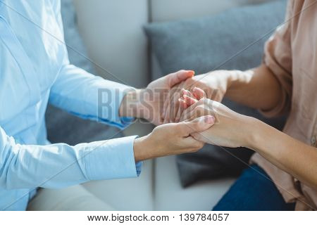 Midsection of therapist holding patient hands on sofa at home