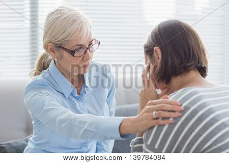 Therapist comforting patient on sofa at home