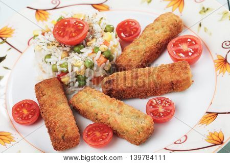 Breaded vegetable sticks served with cooked rice and cherry tomato