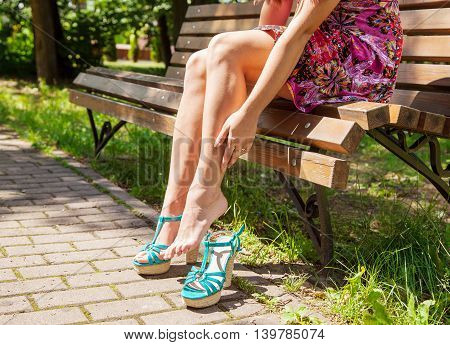 woman stroking her leg while sitting on a park bench on summer day. legs closeup