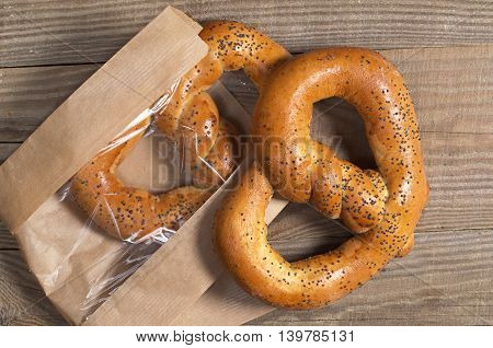 Fresh pretzels with poppy seeds in paper packaging on wooden table top view
