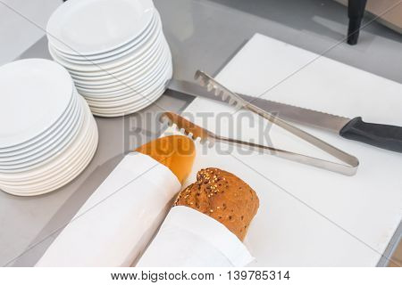Fresh bread slice and cutting knife on table in buffet