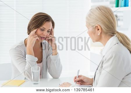 Therapist listening to young woman in office