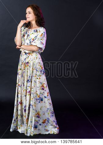 Beautiful Russian woman in long summer dress in a rustic style