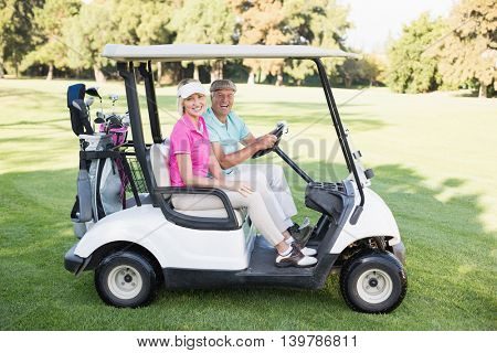 Portrait of happy mature couple sitting in golf buggy