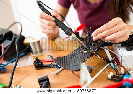 Woman welding the drone body