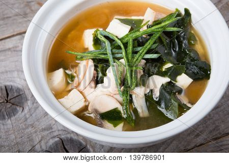Asian tofu soup with seaweed served in a white bowl