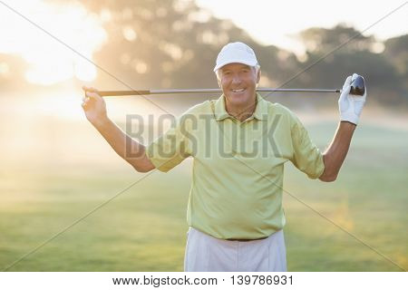Portrait of smiling mature golfer carrying golf club while standing on field