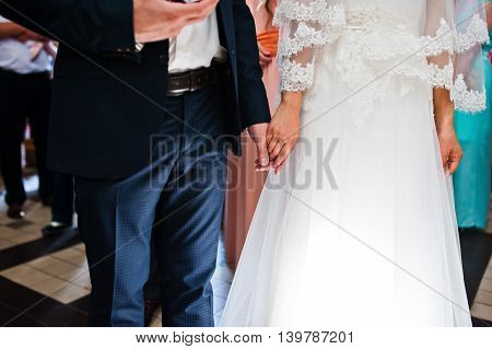 holding hand of newlywed on church at wedding