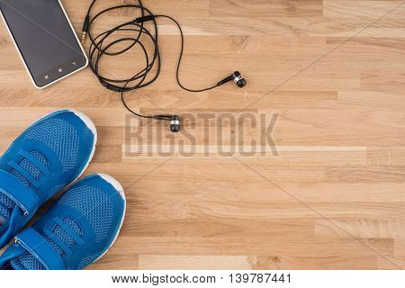 Flat lay shot of Sport equipment. Sneakers earphones and phone on wooden background.