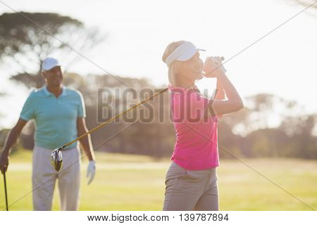 Smiling mature golfer playing by man standing on field