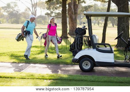 Full length of mature golfer couple by golf buggy while walking on field